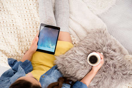 Self-employed girl holding cup of coffee on fur pillow and using tablet for blogging while sitting on bed Stock Photo