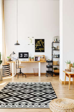 Modern atelier of creative hipster with desk, computer, storage cart and patterned black and white rug lying on hardwood floor Stock Photo