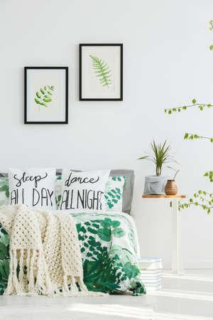 Lascia dipinti su muro bianco sopra il letto con coperta in maglia beige e biancheria da letto floreale in camera da letto con pianta e bombilla sul tavolo Archivio Fotografico - 85280785