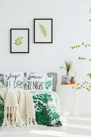 Leaves paintings on white wall above bed with beige knit blanket and floral bedding in bedroom with plant and bombilla on table