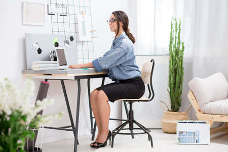 85280786 - Mujer en camisa de mezclilla y falda negra trabajando de forma  remota mientras escribe en la computadora portátil en casa c9ebfa8e9e66