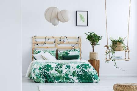Lampen boven bed met bloemenoverlay in eenvoudige slaapkamer met met de hand gemaakte schommeling en kleine boom in pot op houten ontwerperlijst