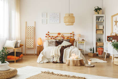 Big wooden lampshade hanging in a bright bedroom Stock Photo