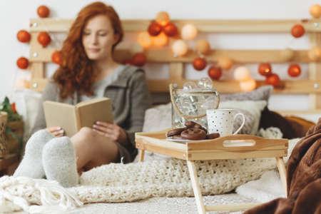 편안한 침대에서 책을 읽고 젊은 여자