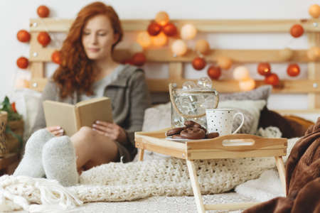 Young woman relaxing and reading a book in bed Stockfoto
