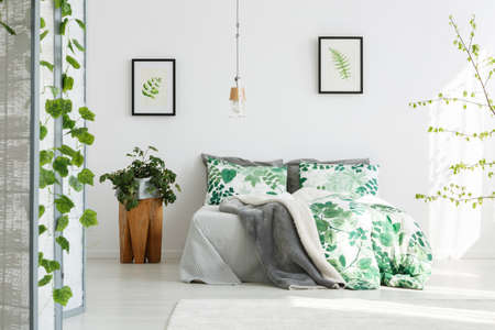 Plant On Wooden Designer Table Next To King Size Bed With Floral Bedding In  Green