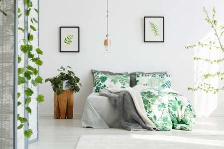 Planta en la mesa de madera de diseño junto a la cama king-size con ropa de cama floral en dormitorio verde con lámpara hecha a mano Foto de archivo - 85280977