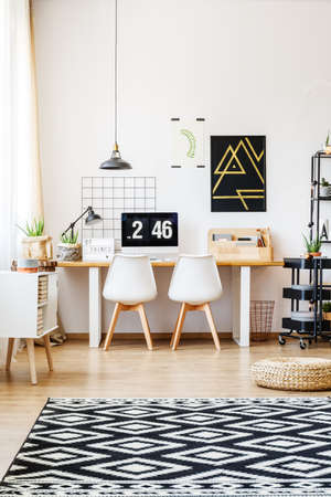 Stylish patterned rug, wicker pouf and natural accessories in modern apartment with white wall and scandinavian design of desk workspace