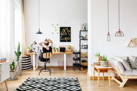 젊은 프리랜서 여자 디자이너 집 멀리에서 펜 던 트 램프, 흰 벽, 큰 창, 편안한 소파와 나무 복고풍 테이블에 서있는 알로에 공장 아늑한 흰색 사무실