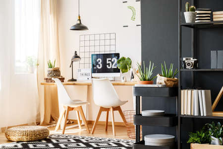 living room window: Modern bright scandi interior full of plants with wooden desk, white chairs and metal furniture standing against trendy black wall
