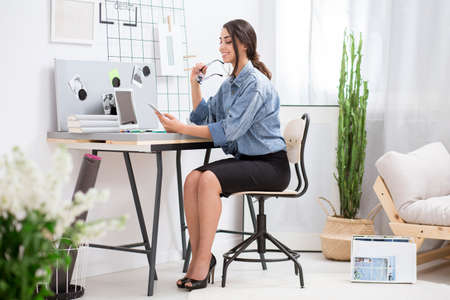 Pretty freelancer using laptop and phone during work at home workspace with cactus Stock Photo