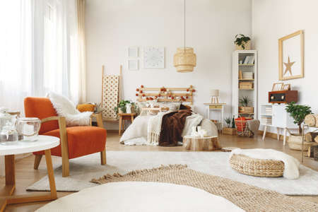 Big comfy orange chair in a bright spacious bedroom