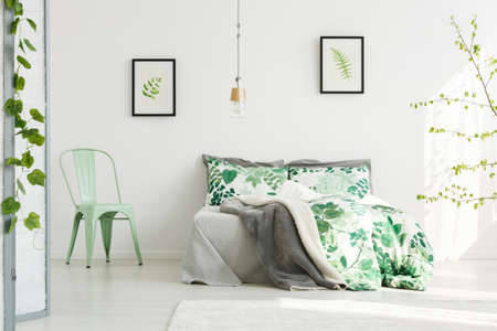 Mint chair next to king-size bed with floral bedsheets in inspiring bedroom with leaves paintings Stock fotó