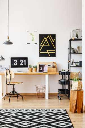 Natuurlijk decor van Skandinavische studiebureauwerkruimte met houten meubilair, retro stoel, installaties, lampen en computer met digitale Desktopklok