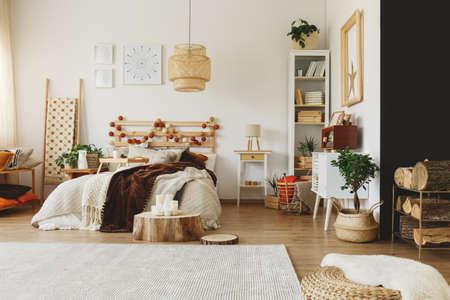 広々 とした居心地の良いベッドルームに置かれた木製のピースをカットします。
