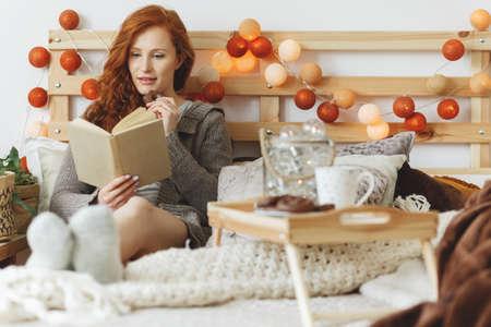 本を読みながらチョコレートのジンジャーブレッドのクッキーを食べる若い女性