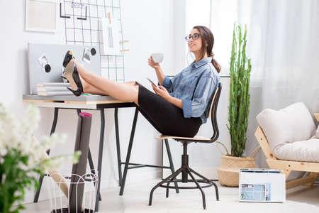 Satisfecho empresaria beber café y mantener sus pies sobre el escritorio durante el descanso en casa Foto de archivo - 85281219