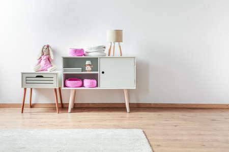Pluchen konijnspeelgoed op wit nachtkastje naast kast met roze gebreide dozen en lamp Stockfoto