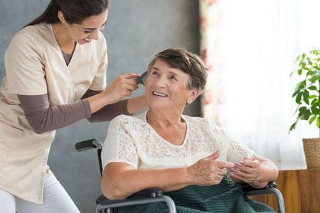 정력적 인 자원 봉사자가 연금 수령자의 머리카락을 닦고, 그녀를 가족 방문을 위해 준비시킵니다. 스톡 콘텐츠 - 85530291