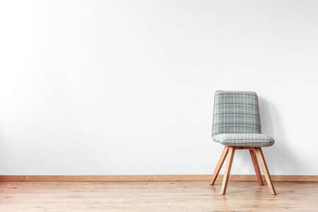 Grey patterned chair on wooden floor in spacious room with white wall Stock fotó