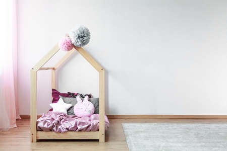 Tulle pompons on wooden kids bed with pink satin bedding and creative pillows in spacious bedroom Stock fotó - 85531918