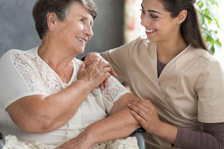 베이지 색 유니폼과 노인 아가씨가 함께 은퇴 가정에서 오후에 보내는 젊은 간호사 스톡 콘텐츠