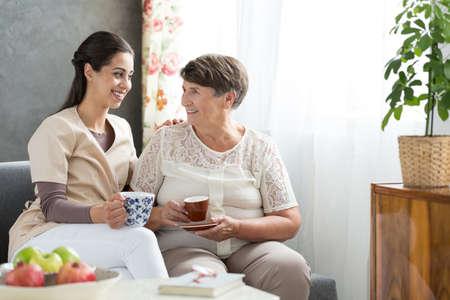 Grateful senior lady serving tea to a helpful nurse visiting her at home after hospitalization