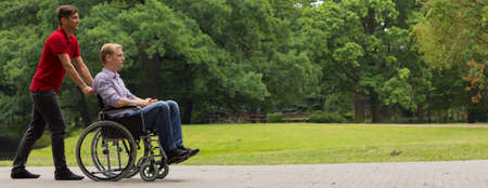 Common walk with disabled friend on wheelchair Stock Photo