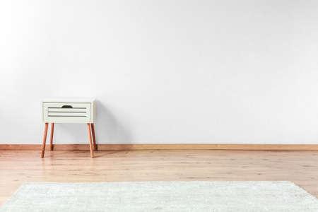 Wit nachtkastje op houten vloer in open plek met wit tapijt en witte muur Stockfoto