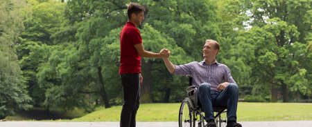 Disabled man greeting with friend in the park Stock fotó