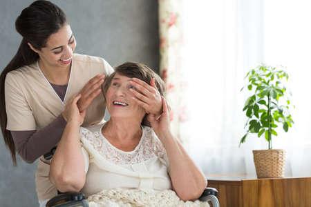 Granddaughter volunteering in a retirement home surprising her grandmother after work Stock Photo