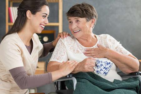 退職女性は車椅子と花柄の白いマグカップからお茶を飲んで話をハッピー ナース 写真素材
