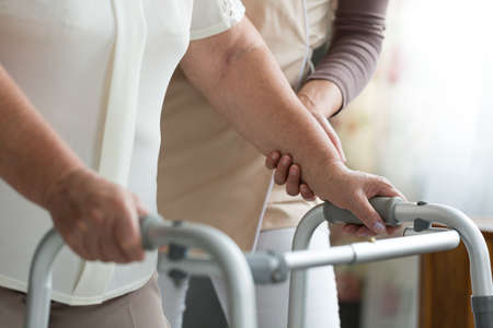 Elder woman trying to walk using a walker during physiotherapy with support of a nurse Banco de Imagens