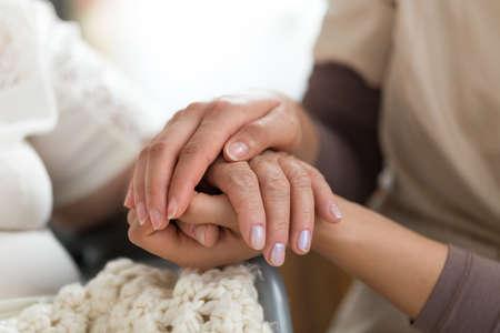女性介護者と手を繋いでいる年配の女性のクローズ アップ写真。介護の概念。