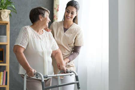特別養護老人ホーム歩くのシニア女性を助ける看護師の笑顔
