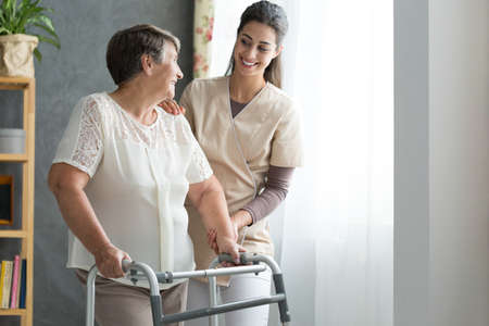 Smiling nurse helping senior lady to walk around the nursing home