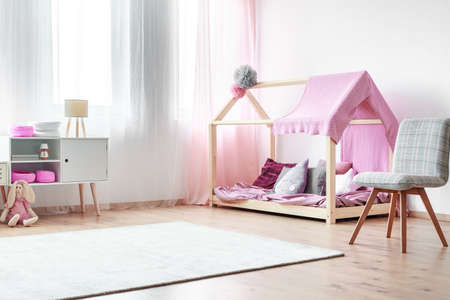 Charming girls bedroom with handmade bed with pink bedsheets and grey chair