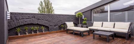 Vista panorámica de la moderna terraza en la azotea con piso de madera oscura, plantas, valla de ladrillo y muebles de jardín negro Foto de archivo - 85705157