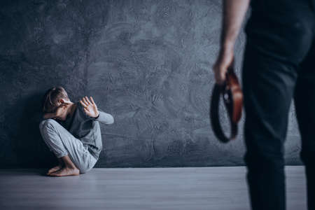 Family violence concept, father wants to beat son with belt
