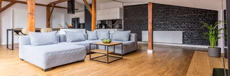 Modern loft open ruimte appartement met houten balken en vloer, eenvoudig modern meubilair, grijze bank, salontafel, bakstenen muur, uitzicht vanuit de woonkamer