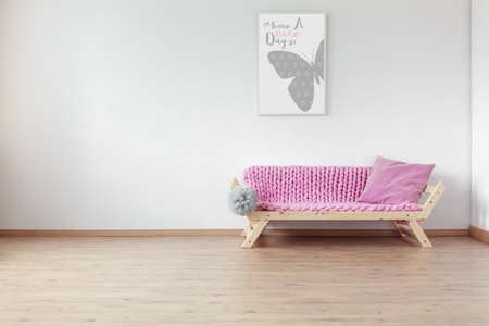 Pink pillow on wooden sofa with braided blanket in empty simple kid room