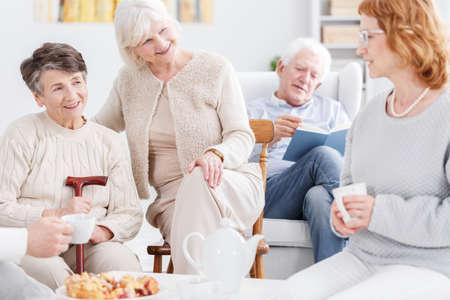 Leute in den großen Stimmungen am Pflegeheim, drei ältere Frauen, die ein nettes Gespräch haben, während ein älterer Mann Buch im Hintergrund liest Standard-Bild - 86163862