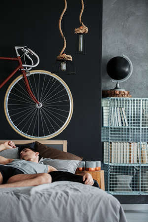 Man is sleeping on king-size bed in manly bedroom with metal shelf and red bike against black wall