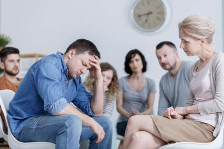 Anxious man holding his head during conversation in support group in room with clock Stock Photo