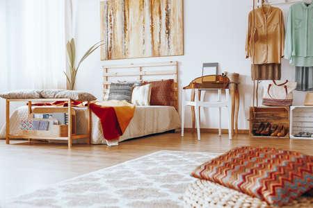 Gedessineerde kussen op materiële poef in zanderige slaapkamer met houten kaptafel Stockfoto