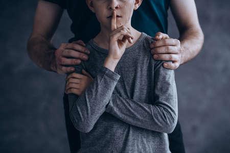 Gesto de silencio, niño maltratado sosteniendo por hombre llorando