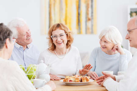 Old age, friendship and people concept, group of attractive happy seniors chatting and having fun together in a cafe Stock Photo