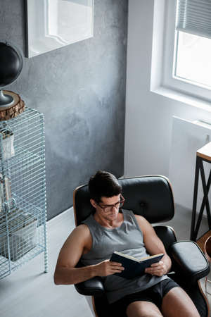 Handsome man works at home while sitting on black leather chair in room with black globe Lizenzfreie Bilder