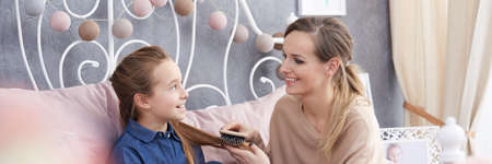 Pretty happy young woman brushing her teenage daughters hair