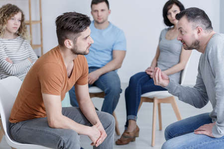 Psychologist talking to young man in supportive AA group Stock Photo